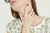 Sore throat, Young woman holding her throat, studio shot