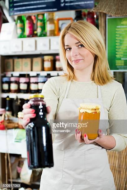 Young woman holding homemade jam and juice at shop