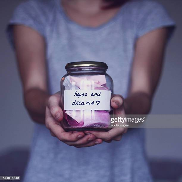 Young woman holding jar with hopes and dreams
