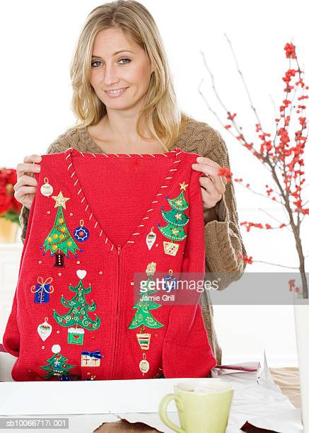 Young woman holding jumper, smiling, portrait