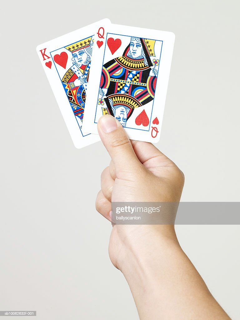Young woman holding king and queen of hearts playing cards, close-up of hand, studio shot : Stock Photo