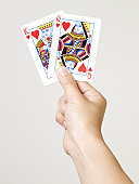 Young woman holding king and queen of hearts playing cards, close-up of hand, studio shot