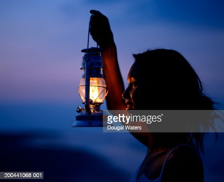 Young woman holding lamp, light highlighting facial features, profile