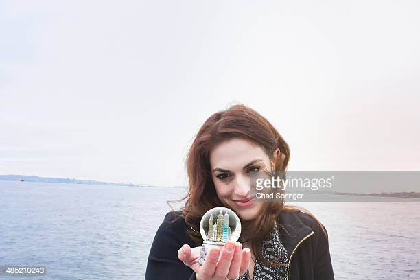 Young woman holding landmark snow globe, New York, USA
