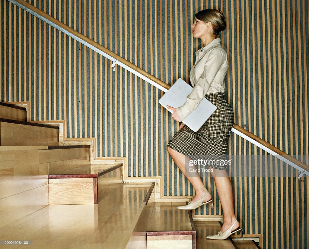 Young woman holding laptop, walking upstairs : Stock Photo