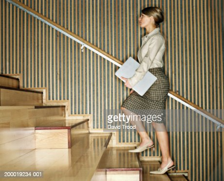 Young woman holding laptop, walking upstairs