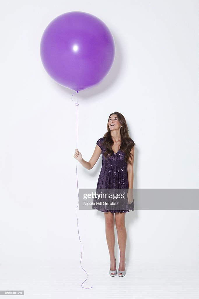 Young woman holding large balloon at party