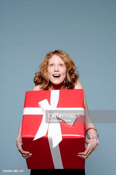Young woman holding large gift box with both arms, looking upwards