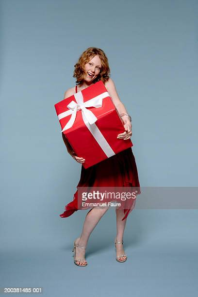 Young woman holding large gift box with both arms, smiling