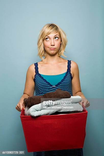 Young woman holding laundry basket and looking up