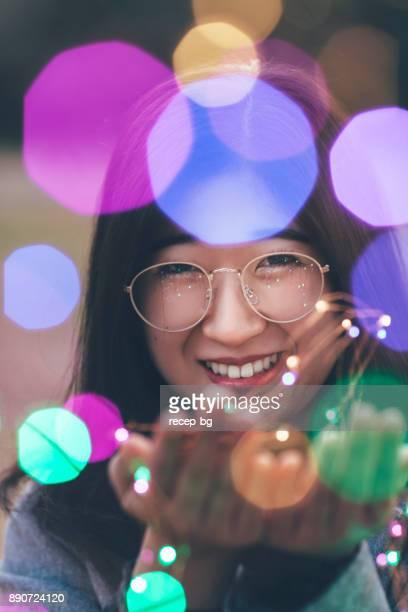 LED ライトを持つ若い女性