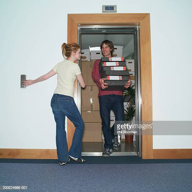 Young woman holding lift door open for male colleague