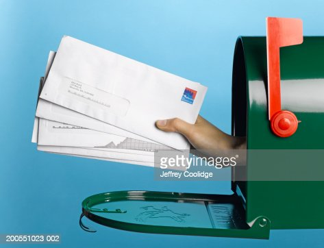Young woman holding mail out of mailbox, side view : Stock Photo