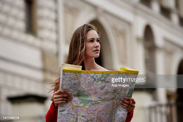 young woman holding map and looking away