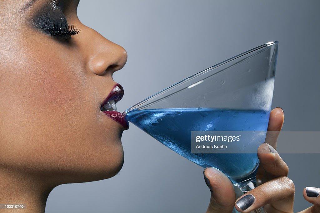 Young woman holding Martini glass touching lips. : Stock Photo