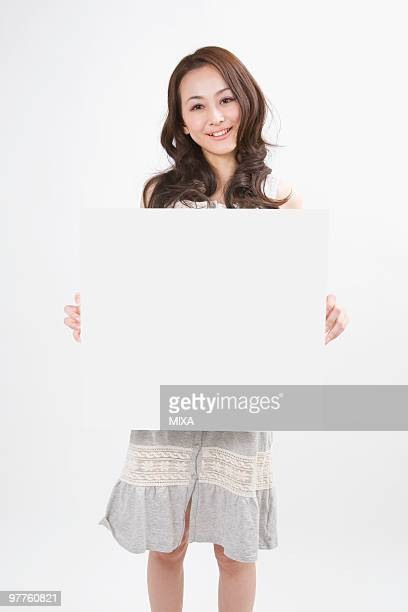 Young woman holding message board