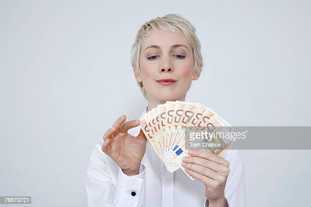 'Young woman holding money, portrait'