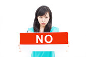 """Beautiful young woman in green dress showing """"NO"""" sign board, isolated on white background."""