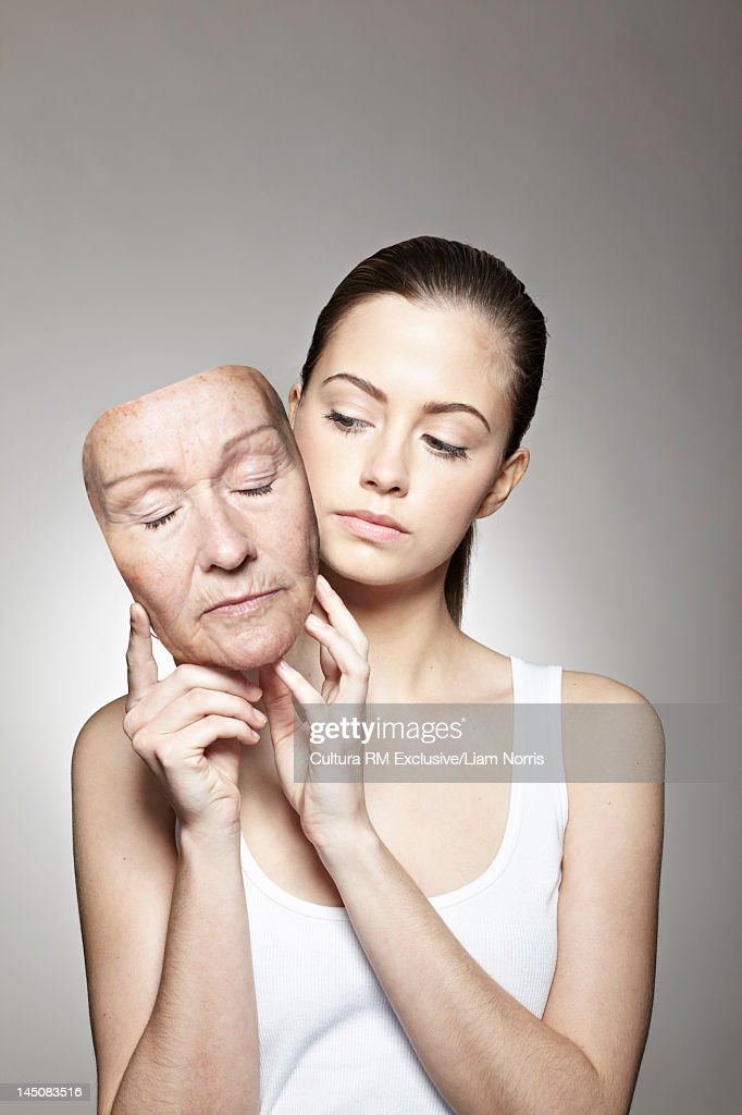 Young woman holding old mask : Stock Photo