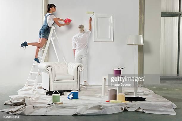 Jeune femme tenant Pot de peinture au-dessus de la tête homme