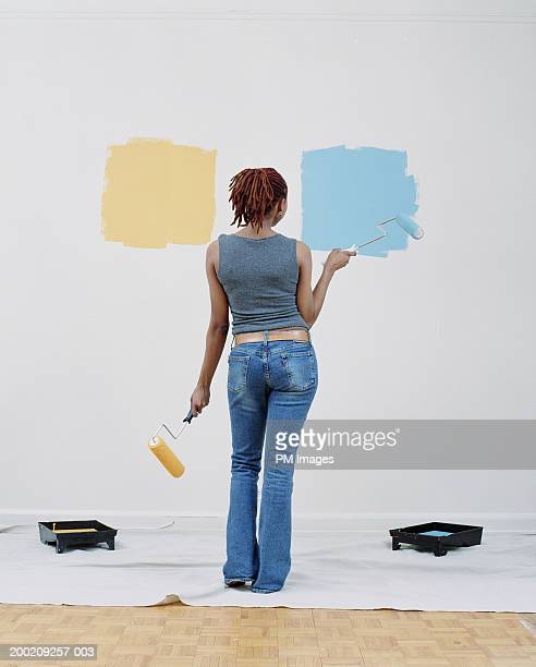 Young woman holding paint rollers, looking at wall, rear view