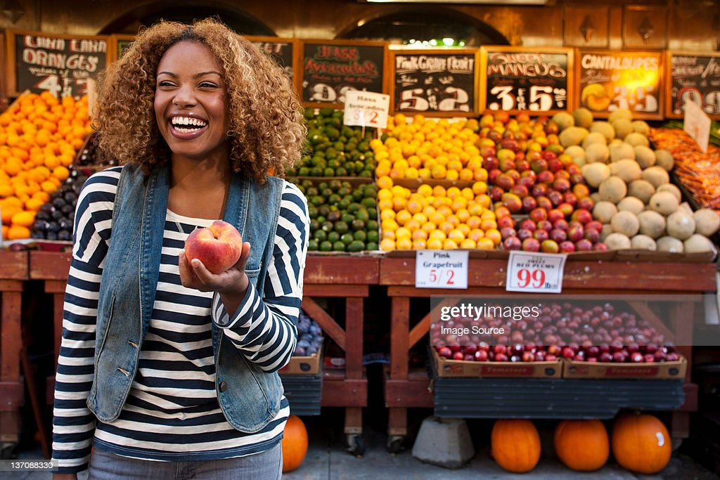Young woman holding peach from market stall, smiling : Stock Photo