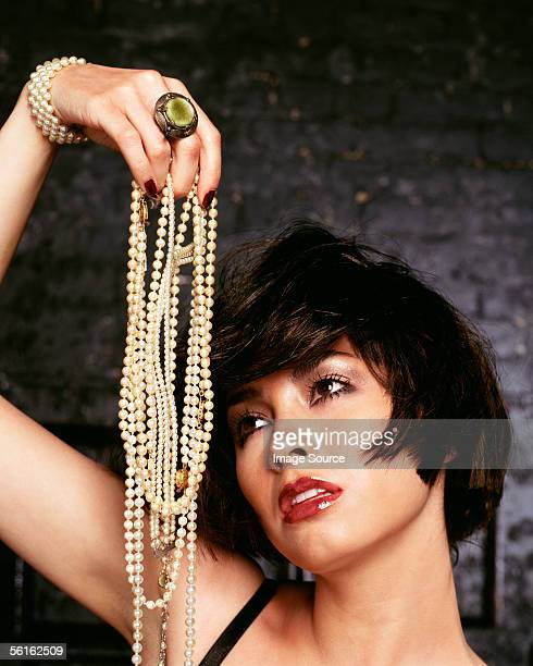 Young woman holding pearl necklaces