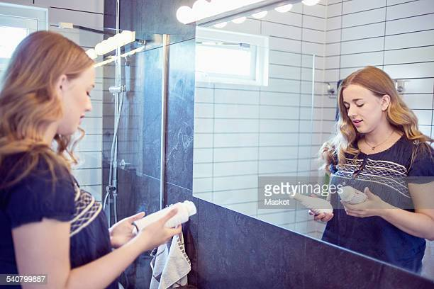Young woman holding perfume bottles in front of bathroom mirror
