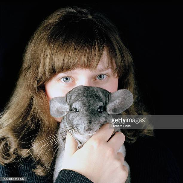 Young woman holding pet chinchilla in front of face, portrait