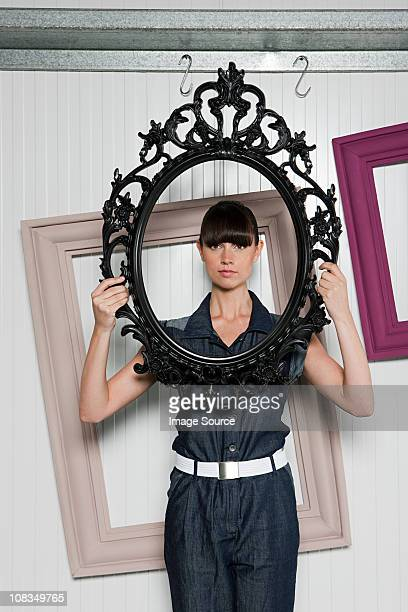 Young woman holding picture frame