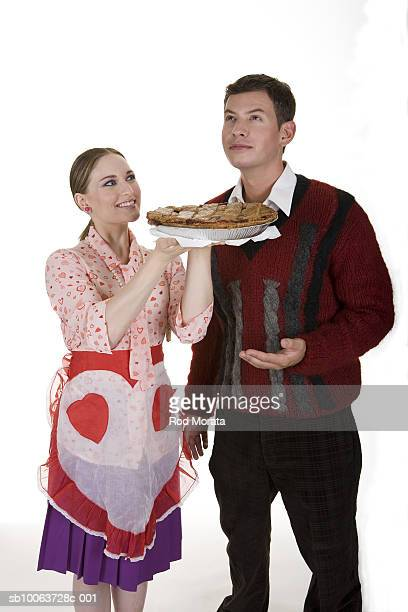 Young woman holding pie to man, smiling