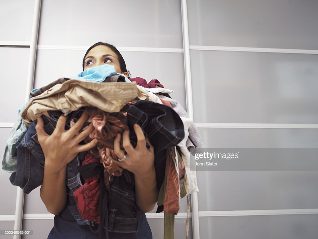 Young woman holding pile of laundry, low angle view