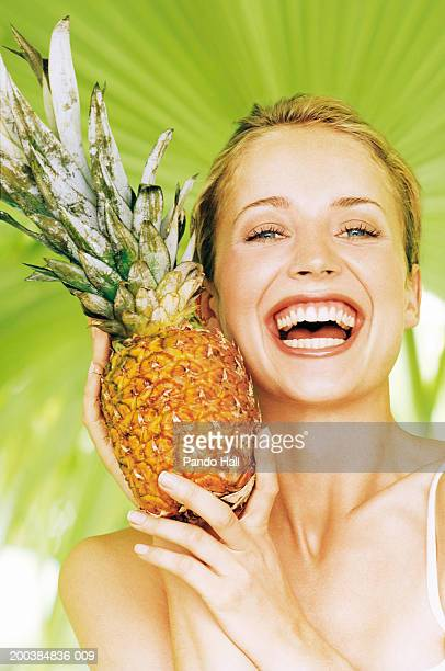 Young woman holding pinapple, laughing, close up, portrait