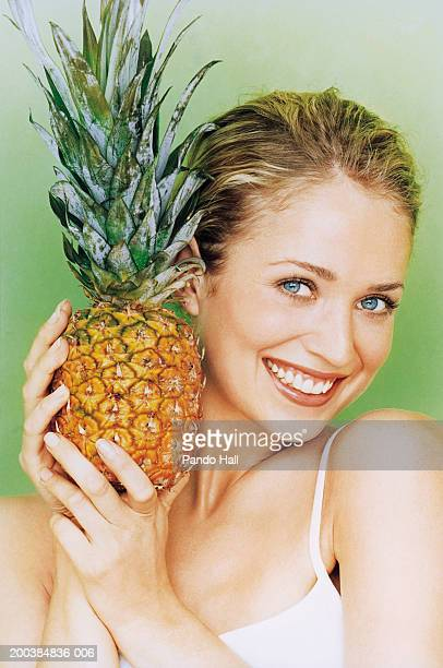 Young woman holding pineapple, smiling, close up, portrait