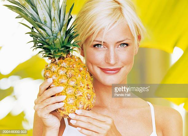 Young woman holding pineapple, smiling, close-up, portrait