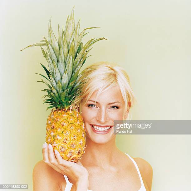 Young woman holding pineapple, smiling, portrait