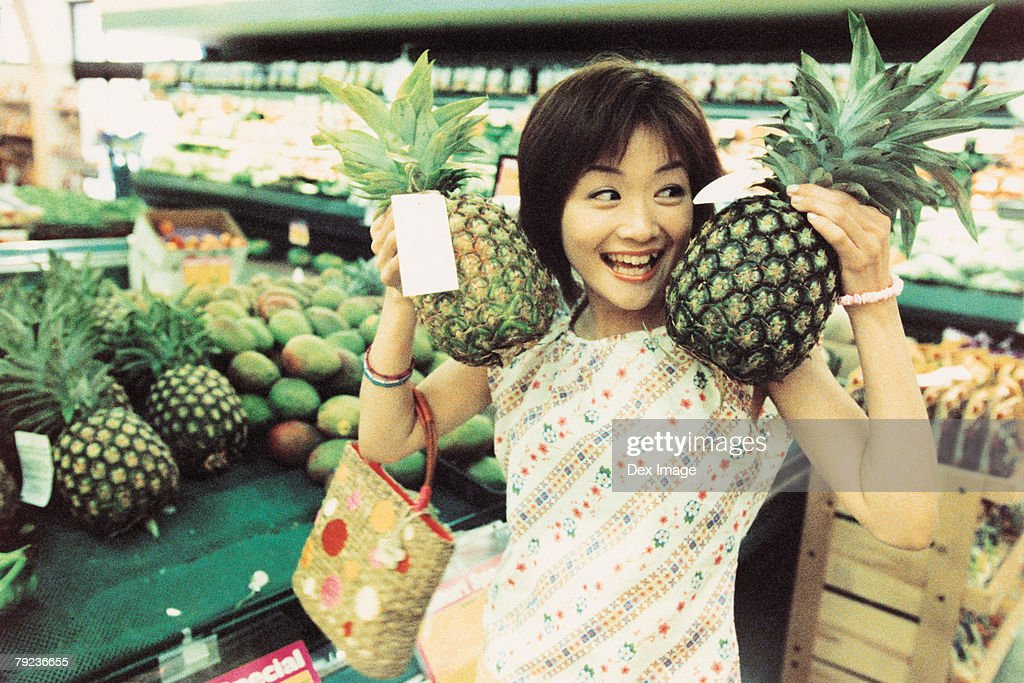 Young woman holding pineapples in fruit store : Stock Photo