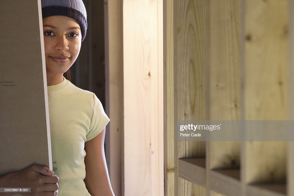 Young woman holding plank of wood, portrait : Stock Photo