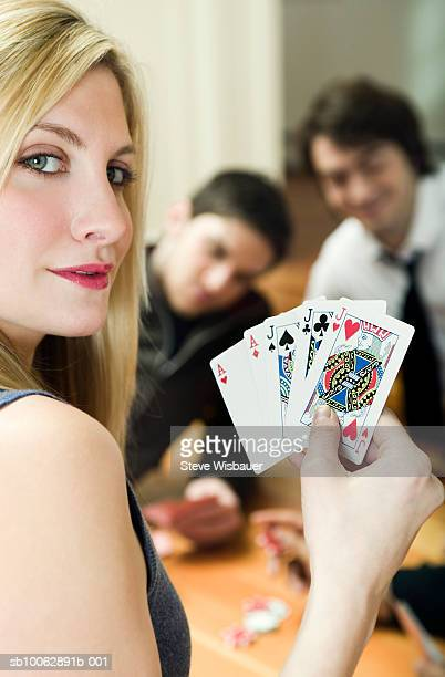 Young woman holding playing cards, in casino