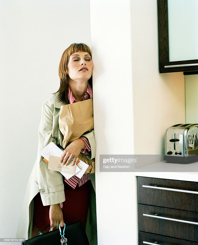 Young woman holding post and bags leaning against wall, eyes closed