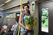 Young woman holding potted plant in train
