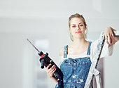 Young woman holding power drill standing on ladder, portrait