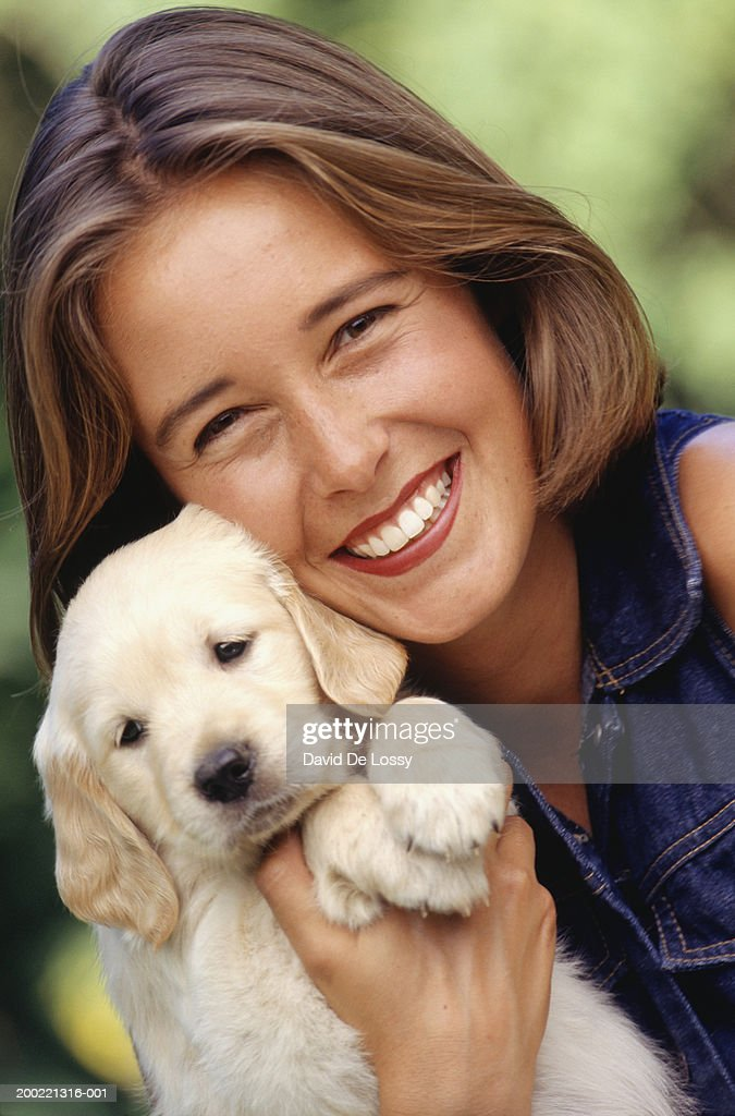 Young woman holding puppy, portrait : Stock Photo