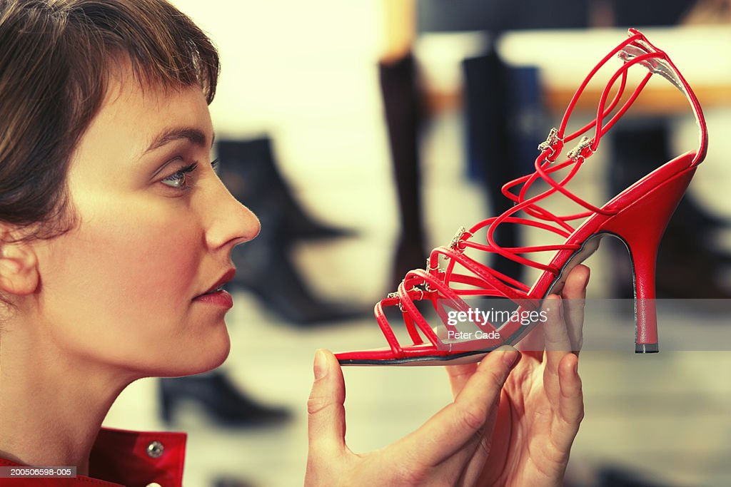 Young woman holding red high heel, close-up