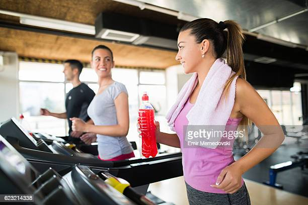 Young woman holding refreshment drink while exercising on treadmill.