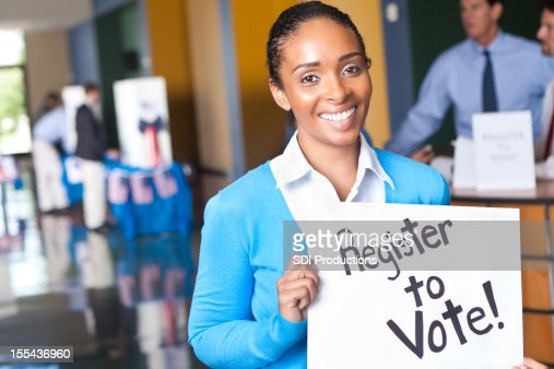 Young woman holding register to vote sign at voting center