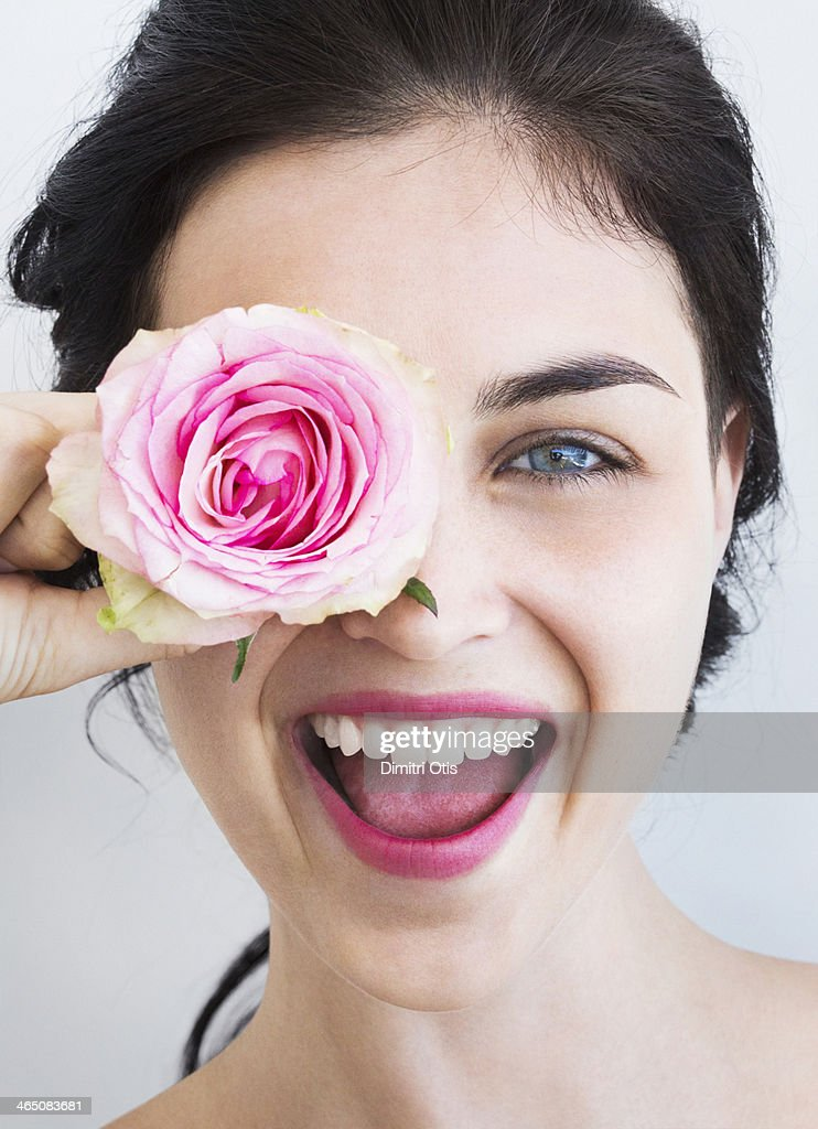 Young woman holding rose to her face, laughing