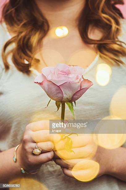 Young woman holding rose with bokeh