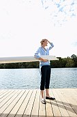 Young woman holding sail boom on pier