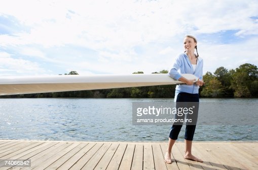 Young woman holding sail boom on pier : Stock Photo
